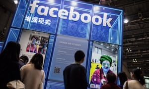 Visitors walk past a Facebook sign during the China International Import Expo in Shanghai