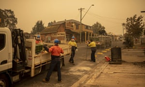 Workers erect fences in front of destroyed buildings in the main street of Cobargo, NSW.