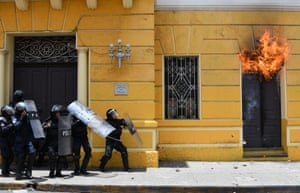 Riot policemen stand outside the municipal palace after demonstrators set it on fire during a May Day protest demanding the resignation of president Juan Orlando Hernandez.