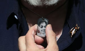 Close-up image of a man's hand holding a black-and-white photograph on a pendant around his neck