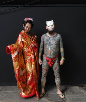 Tattooed visitors pose for photographs during the London Tattoo Convention