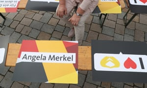 A woman sits among election campaign signs in Germany.