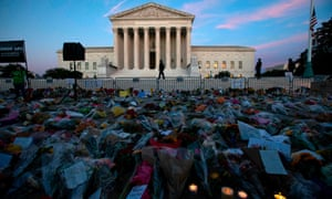 Flowers, candles, and signs are pictured at a memorial outside the supreme court.