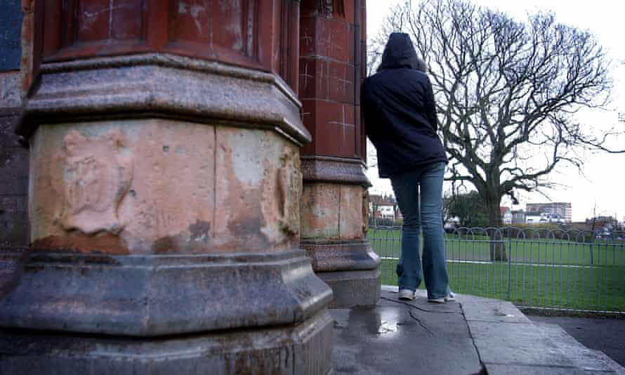 Young person with hood up and back to camera in park
