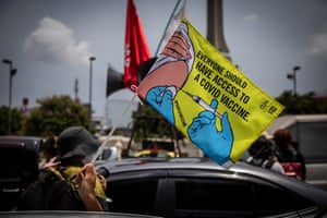 """A pro-democracy protester waves a flag reading """"Everyone should have access to a COVID vaccine"""" in Bangkok, Thailand."""