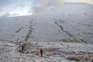 People out and about on the path that leads from Storey Arms to the top of Pen y Fan in the snow-covered Brecon Beacons