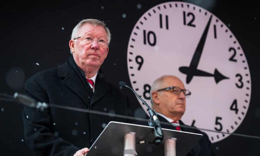 Sir Alex Ferguson gives a reading in front of a clock displaying the time of the crash.
