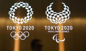 A man walks past the logos of the Tokyo 2020 Paralympics and Olympics.