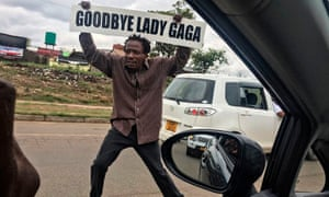 A man carries a sign referencing Zimbabwe's first lady, Grace Mugabe
