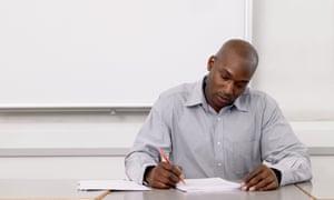 A black male teacher marks essays