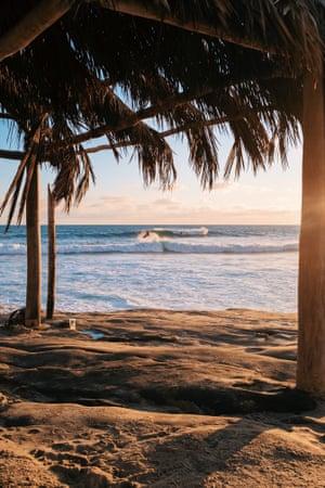 A surfer framed by the palm frond hut at Windansea beach, in La Jolla.