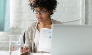 Women working at desk behind a laptop