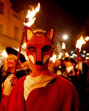 A fox–masked parade attendee is illuminated by the flames in Lewes