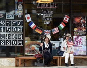 Elderly Japanese women sit under a welcome message outside a shop during the world leaders' visit to the Ise-Jingu Shrine