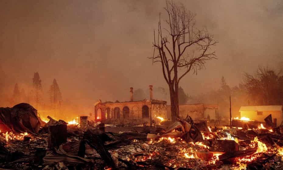 Buildings burn as the Dixie fire tears through the Greenville community of Plumas county, California.