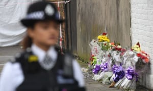 A policewoman stands in front of a floral tribute on a street.
