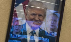 Mugshots of bombing suspect Cesar Sayoc are reflected on a portrait of Donald Trump before a press conference at the Department of Justice in Washington on Friday.