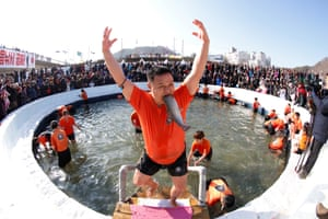 Hwacheon, South Korea. A man celebrates after hand fishing in a frozen river during an ice festival