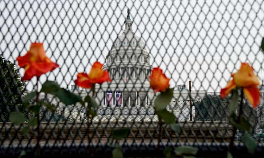 Flowers in security fencing days after supporters of Donald Trump stormed the Capitol