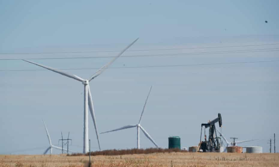 Wind turbines spin as a pump jack pulls up oil in west Texas.