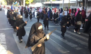 In the parade young girls wore niqab-style black veils and carried cardboard cutouts of guns