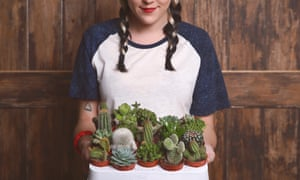 Young woman with tray cacti and succulents
