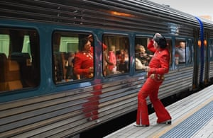 An Elvis fan grooms his hair at a train window before travelling to the Parkes Elvis festival.