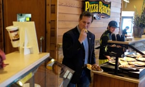Rick Santorum takes a bite of pizza prior to speaking to a small group of people in a meeting room at a Pizza Ranch in Sheldon, Iowa on 20 January.