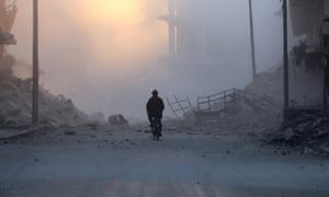 A man cycles near damaged buildings after a strike on the rebel-held al-Shaar area of Aleppo.