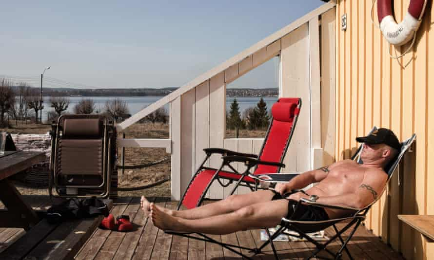 An inmate at Bastøy prison in Norway sunbaths in front of a wooden cottage where he lives in the prison grounds.