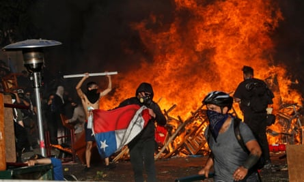 Demonstrators react as fire rages during an anti-government protest in Santiago.