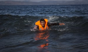 A migrant swims as he arrives on the island of Lesbos after crossing the Aegean sea from Turkey to Greece on an overcrowded inflatable boat this week.
