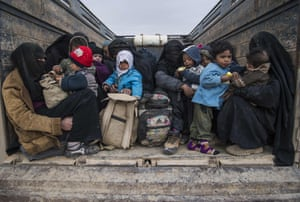 Women and children who fled the Islamic State's embattled holdout of Baghuz on 14 February wait in the back of a truck in the eastern Syrian province of Deir Ezzor.