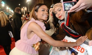 Naomie Harris takes some selfies with fans on the red carpet