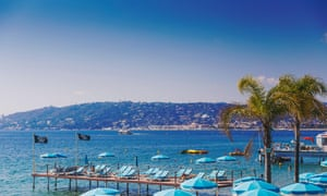 JUAN LES PINS, FRANCE - September 20th, 2016: Blue Mediterranean landscape and French beach with colorful umbrellas shot in Juan Les Pins on the FrencJDE1WK JUAN LES PINS, FRANCE - September 20th, 2016: Blue Mediterranean landscape and French beach with colorful umbrellas shot in Juan Les Pins on the Frenc