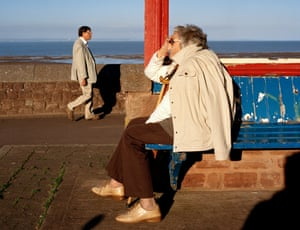 A woman sitting and a man walking along the seafront at Minehead