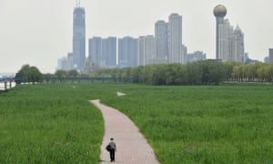 A man wearing a face mask walks at a riverside park in Wuhan of Hubei province, the epicentre of China's coronavirus outbreak, 26 March 2020.