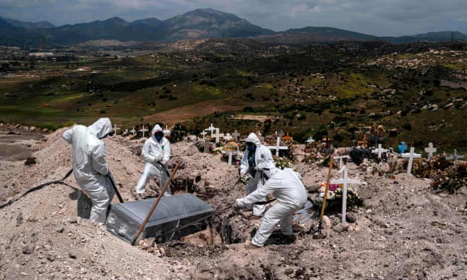 Εργαζόμενοι στο νεκροταφείο που φορούν προστατευτικό εξοπλισμό θάβουν ένα θύμα κοροναϊού στην Τιχουάνα.