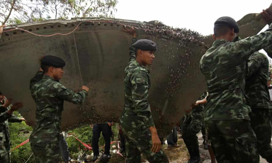 Thai soldiers carry a piece of debris that washed ashore at Nakhon Si Thammarat on 25 January. The metal was not part of missing Malaysia Airlines flight MH370.