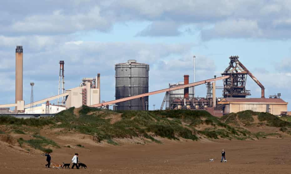 People walk along a beach near the former Corus steelworks in Redcar.
