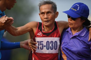 A man in the 75-80 age category being assisted after winning the 400m sprint
