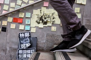A man walks past artwork with protest messages.