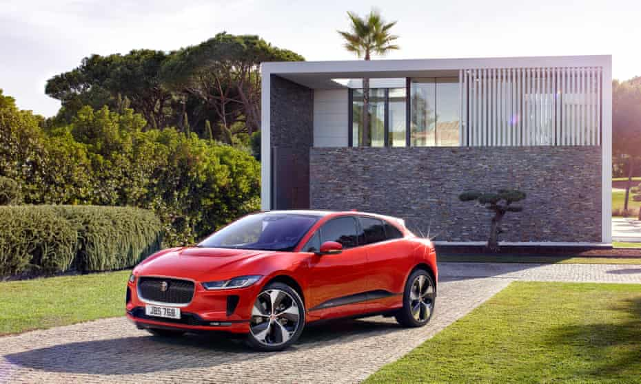 Red Jaguar iPace parked in front of a small shed