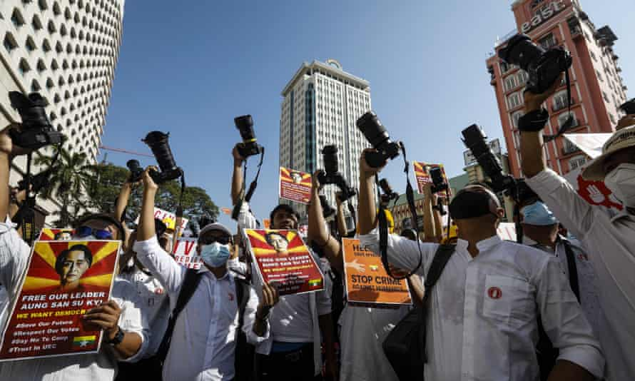 Photographers from the Myanmar Photographers Association hold up their cameras and placards calling for the release of detained Myanmar State Counselor Aung San Suu Kyi during a protest against the military coup in Yangon on 13 February 2021.