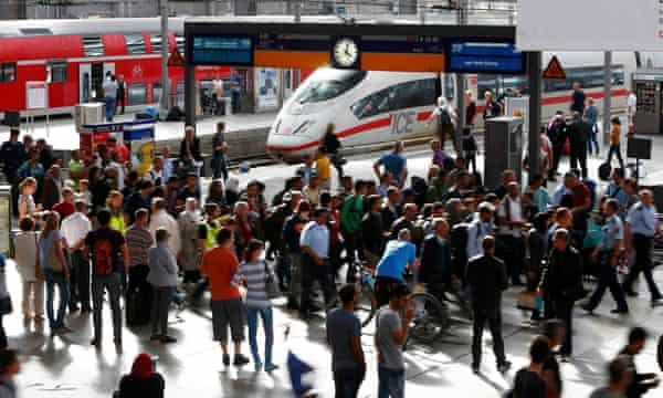 Refugees are escorted by officials at the main railway station in Munich.