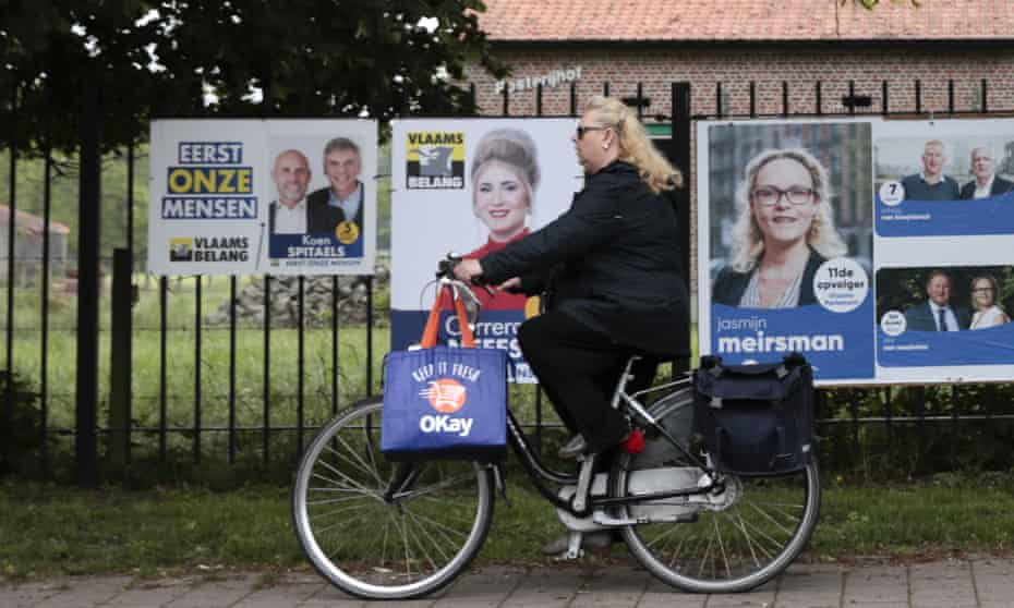 A woman rides her bicycle past campain posters in Wuustwezel, Belgium.