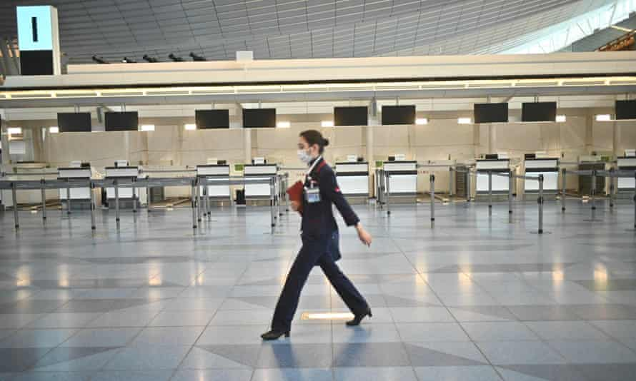An airline employee in a face mask walks in front of closed airline counters at Tokyo's Haneda airport in Japan.
