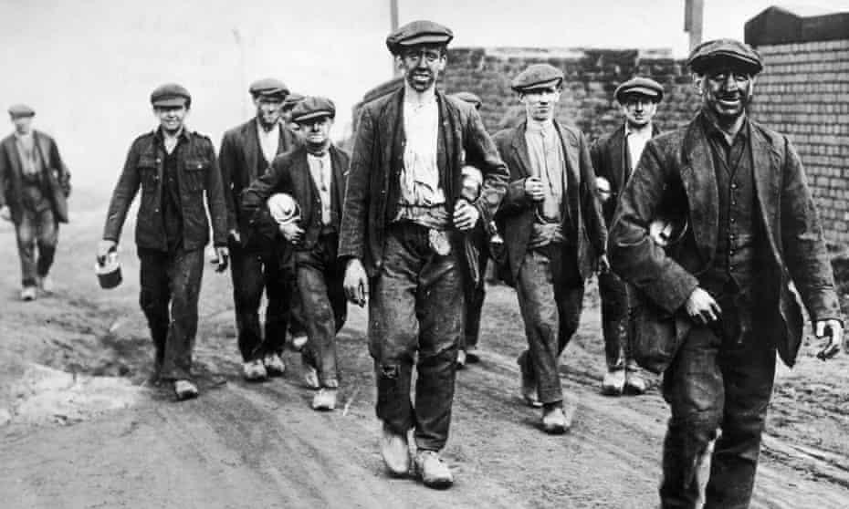 English coal miners walk home from work, circa 1925.