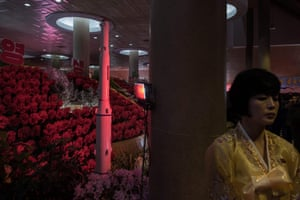 Pyongyang, North Korea A rocket is displayed behind a hostess at a flower show celebrating the 75th anniversary of the birth of Kim Jong-Il