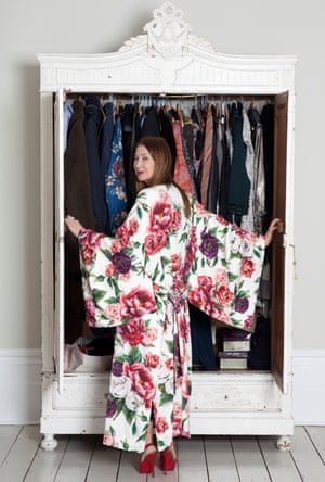 Sharon Walker in a bold floral kimono-type dress and high red shoes opening her wardrobe and looking round at the camera